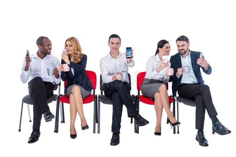 Collègues satisfaits communiquant les uns avec les autres tout en ayant le café image stock