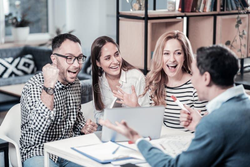 Collègues stupéfaits joyeux ayant l'amusement et la communication image stock