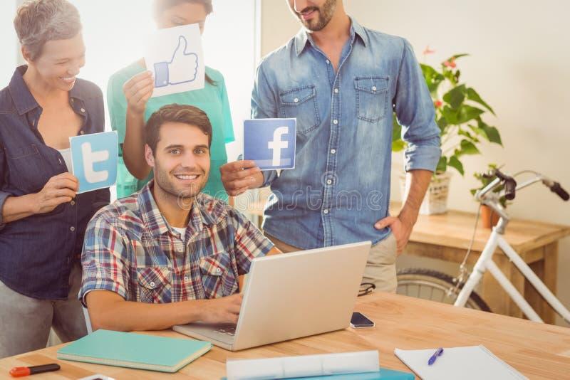 Collègues tenant le signe des réseaux sociaux célèbres photo libre de droits