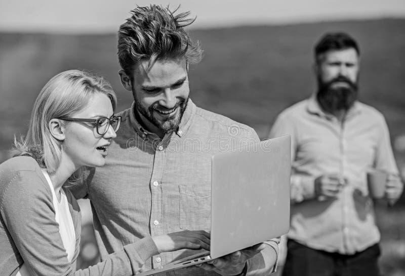 Collègues travaillant l'ordinateur portable, patron fumant tandis que pause-café sur le fond Le couple fonctionne l'outrage de la photo libre de droits