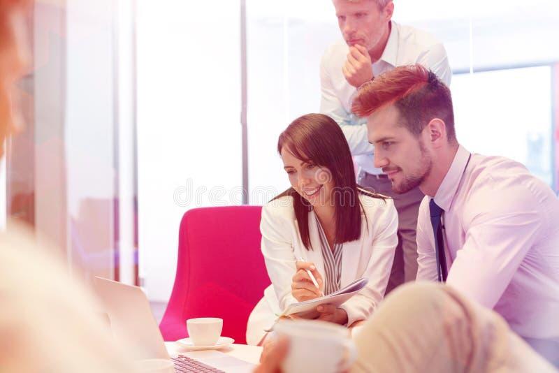 Coll?gues d'affaires discutant au-dessus de l'ordinateur portable dans la salle de r?union au bureau image stock