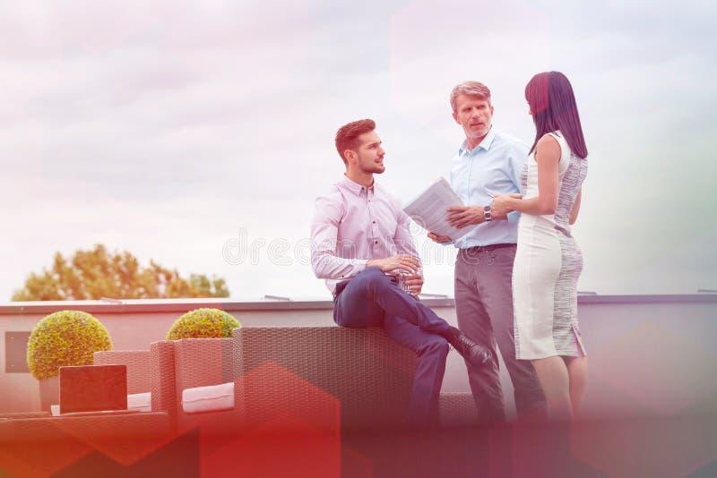 Coll?gues d'affaires discutant au-dessus des documents ? la terrasse de bureau contre le ciel photo stock