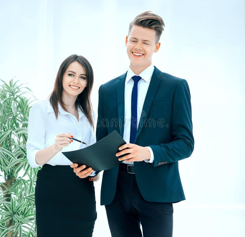 Coll?gues d'affaires discutant des affaires debout de document dans le bureau photographie stock