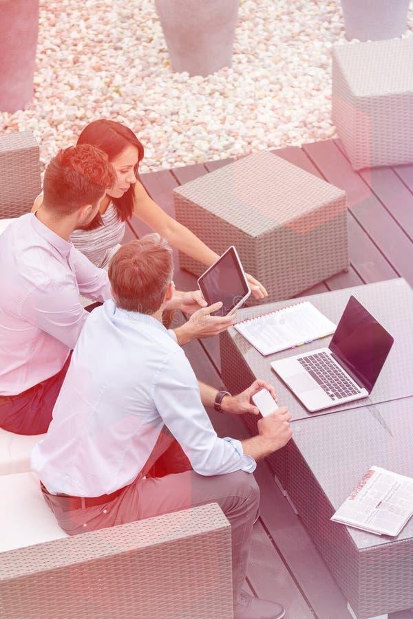 Coll?gues d'affaires employant la technologie se reposant ? la terrasse de bureau photographie stock