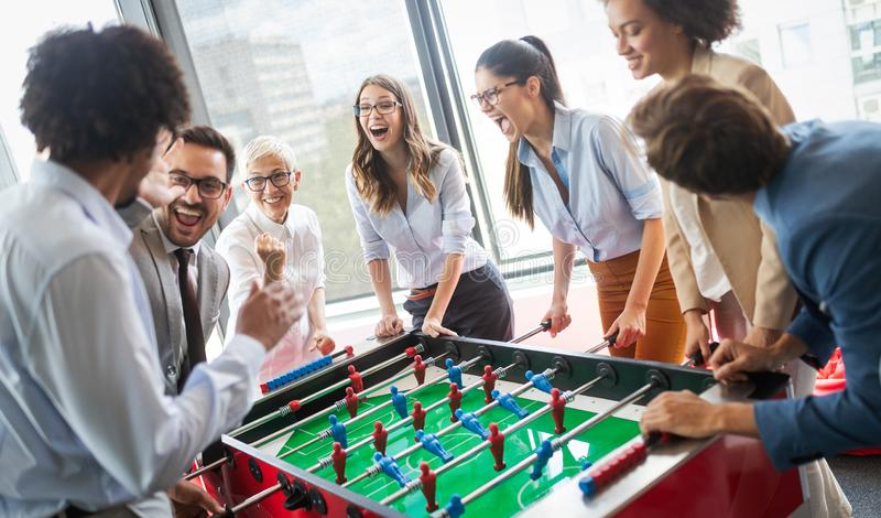 Coll?gues jouant le football de table sur la coupure du travail photos stock