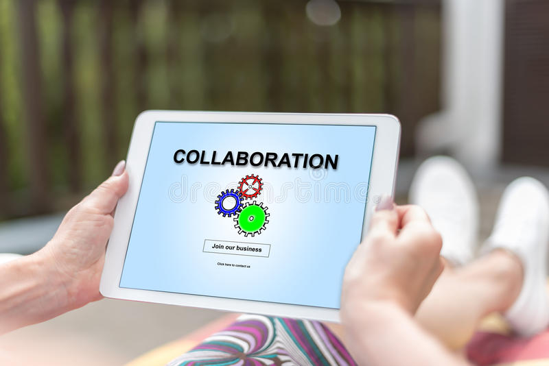 Collaboration concept on a tablet. Female hands holding a tablet with collaboration concept stock photography