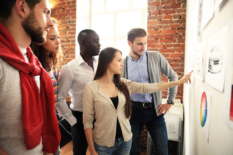 Collaboration is a key to best results. Group of young modern people in smart casual wear planning business strategy stock photography