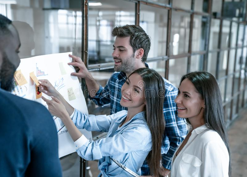 Collaboration is a key to best results. Group of young modern people in smart casual wear planning business strategy while young royalty free stock photography