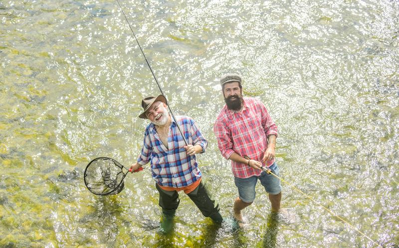 Collaboration. two happy fisherman with fishing rod and net. father and son fishing. Poaching. Camping on the shore of stock photo