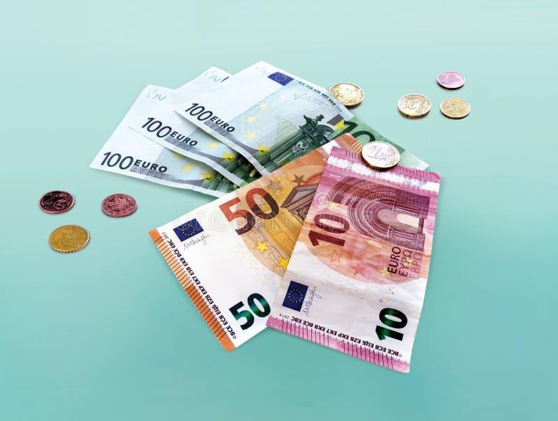 Collage av mynt och eurovalutasedlar på en blå bakgrund royaltyfri foto