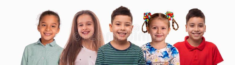 Collage av studioståendena av att le schoolchilds av olika lopp, på vitt royaltyfria foton