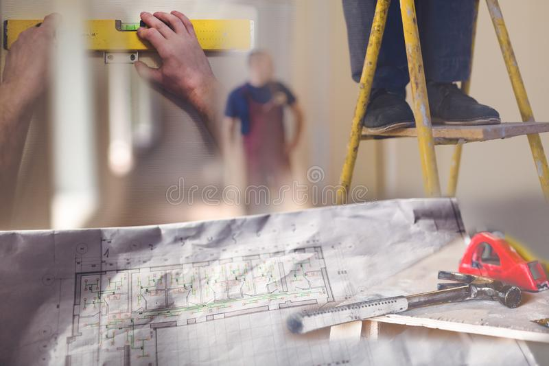 Collage of construction site with architectural plan with details, marked by measurements, construction and design details and. Workers in an apartment during royalty free stock photo