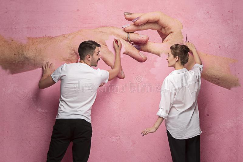 The collage about couple writing something on a pink wall. On the wall my photo of female and male hands. Concept of love and new family royalty free stock image