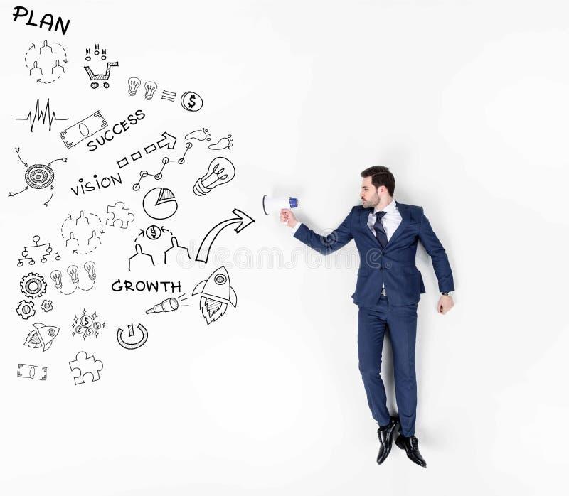 collage creativo del hombre de negocios joven con el altavoz y diversos iconos y muestras del negocio foto de archivo libre de regalías