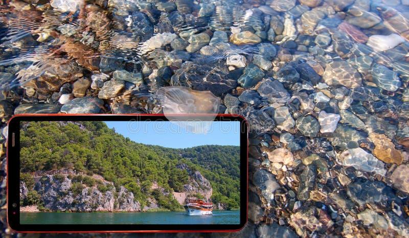 Collage de las medusas soleadas que flotan en agua sobre las piedras del Mar Negro y el teléfono celular que exhibe la naturaleza imagen de archivo