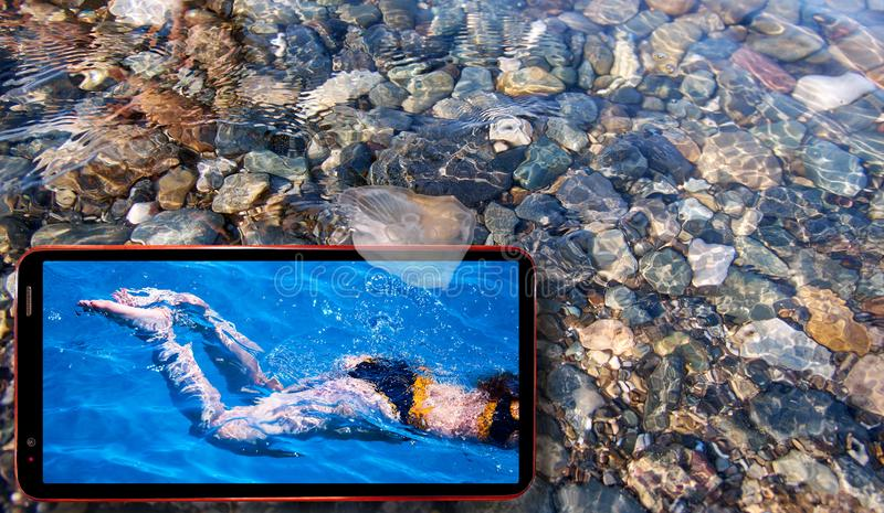 Collage de las medusas soleadas que flotan en agua sobre las piedras del Mar Negro y el teléfono celular que exhibe a muchachas b foto de archivo