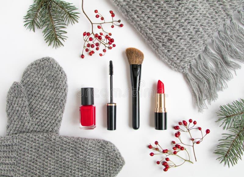 Collage de los accesorios del invierno con los cosméticos y la ropa en el fondo blanco Endecha plana, visión superior fotografía de archivo