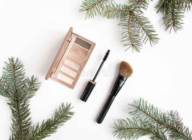 Collage de los cosméticos del invierno adornado con el árbol de abeto en el fondo blanco Endecha plana, visión superior foto de archivo