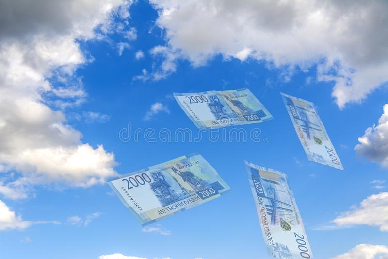 Collage del cielo Espejismo - contra el cielo azul que vuela rublos rusas transparentes Nuevo billete de banco 2000 rublos fotografía de archivo