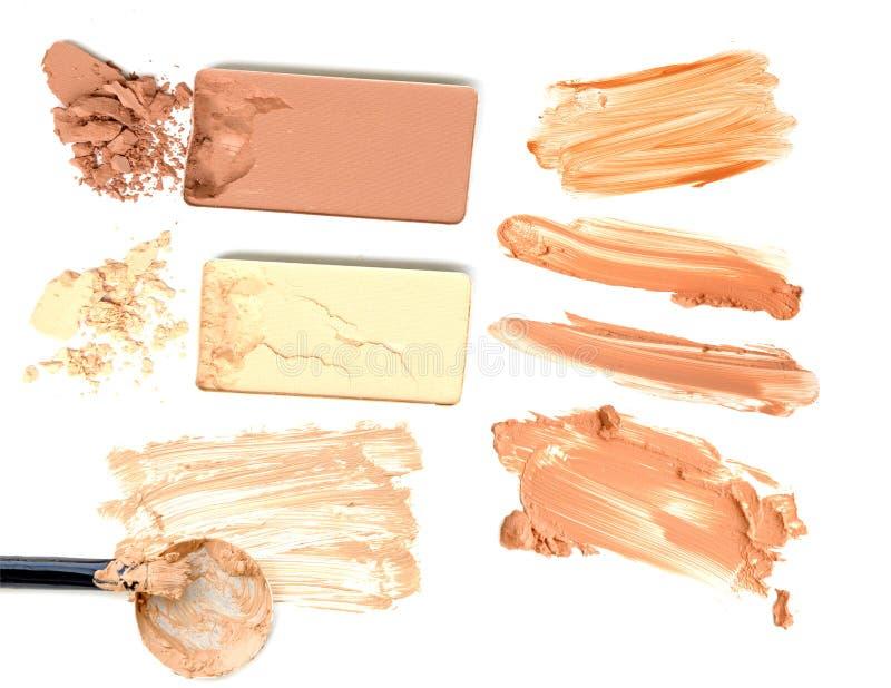 Collage della polvere del fondamento dei cosmetici su fondo bianco Bellezza e concetto di trucco fotografia stock libera da diritti