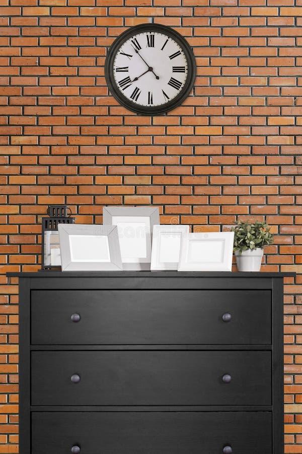 Collage delle cornici sul gabinetto e sull'orologio di legno neri nel emp fotografia stock