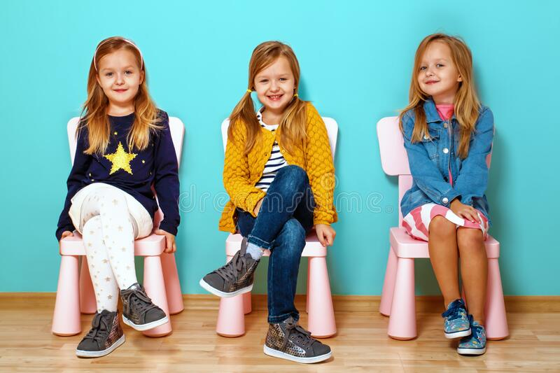Collage of a happy little child girl, in different clothes and moods. Sitting on chairs against a blue background stock image