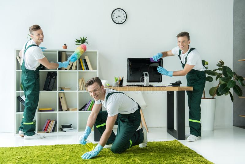 Collage of happy young worker cleaning office and smiling. At camera stock photo