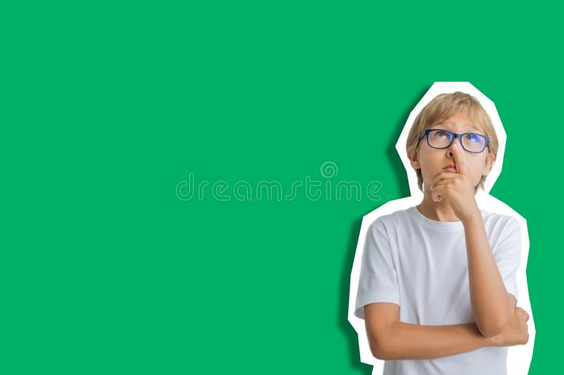 Collage in magazine style on green background. Child emotions. Boy looking up and thinking.  royalty free stock photo