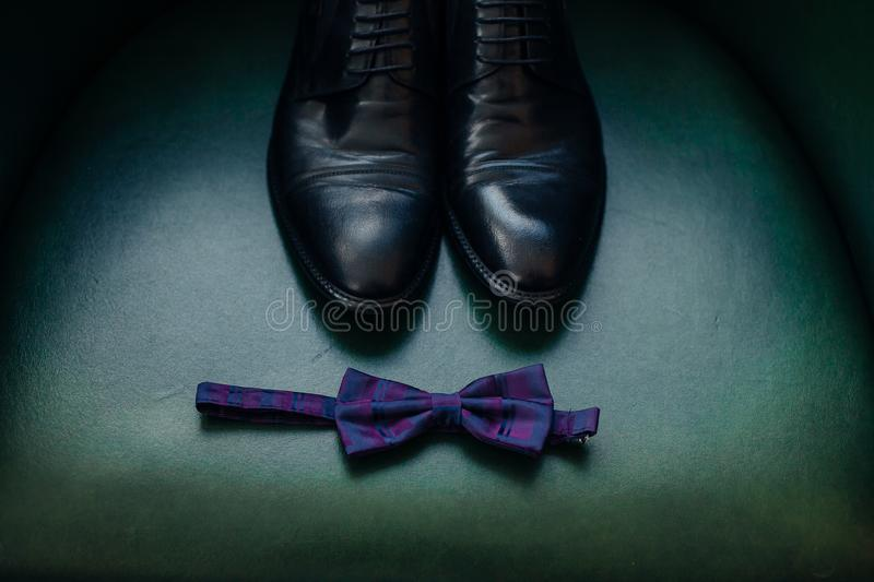 Collage of modern men`s clothing on green background. Groom detail shoes male shoes and bow-tie on green armchair royalty free stock photos