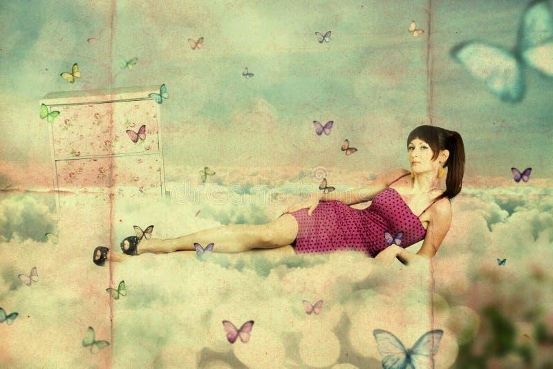 Collage. mujer joven de la belleza en el cielo, en nubes foto de archivo libre de regalías