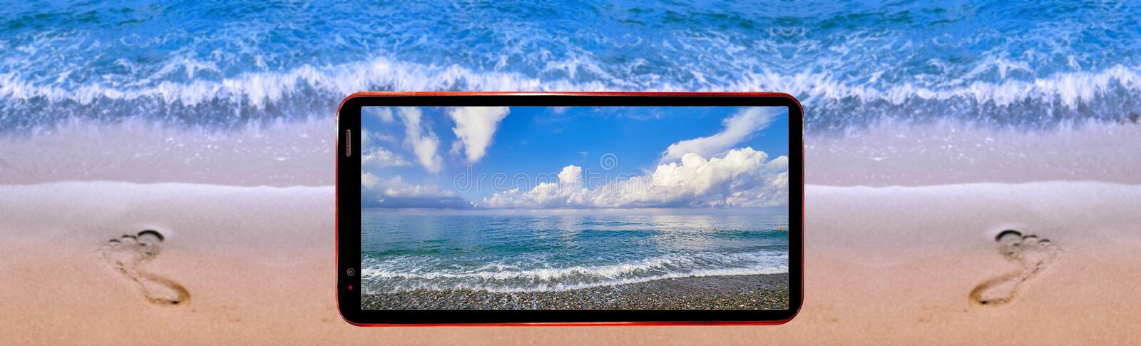 Collage picture of cell phone demonstrating nice sea landscape on screen and blurred background of water edge of sunny beach with royalty free stock photo