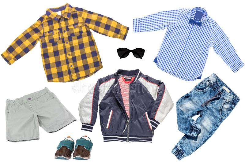 Collage set of children clothes. Denim jeans or pants, shoes, two checkered shirts, rain jacket and shorts for child boy isolated. On a white background royalty free stock image