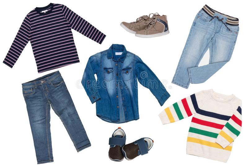 Collage set of children clothes. Denim jeans or pants, two pair shoes, a jeans shirt, striped shirt and a sweater for child boy. Isolated on a white background royalty free stock images
