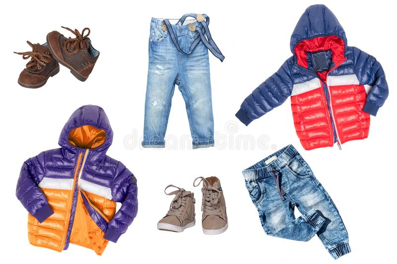 Collage set of children clothes. Denim pants, shoes and warm down jackets for child boy isolated on a white background. Concept. Spring autumn and summer royalty free stock photography