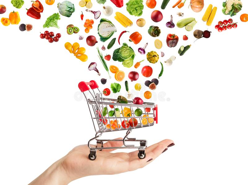 Collage of shopping cart with vegetables and fruits isolated on stock photography