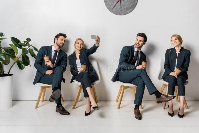 collage of smiling young business people with smartphone and paper cups waiting on chairs stock photography