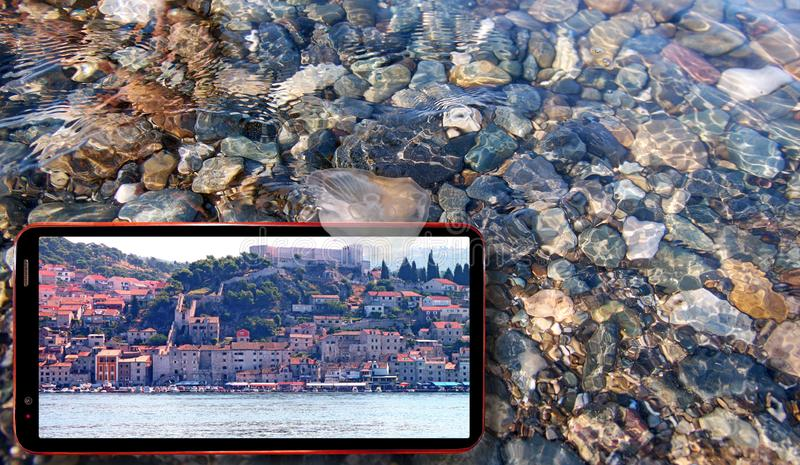 Collage of sunny jellyfish floating in water above Black sea stones and cell phone displaying Croatia nature on screen stock images
