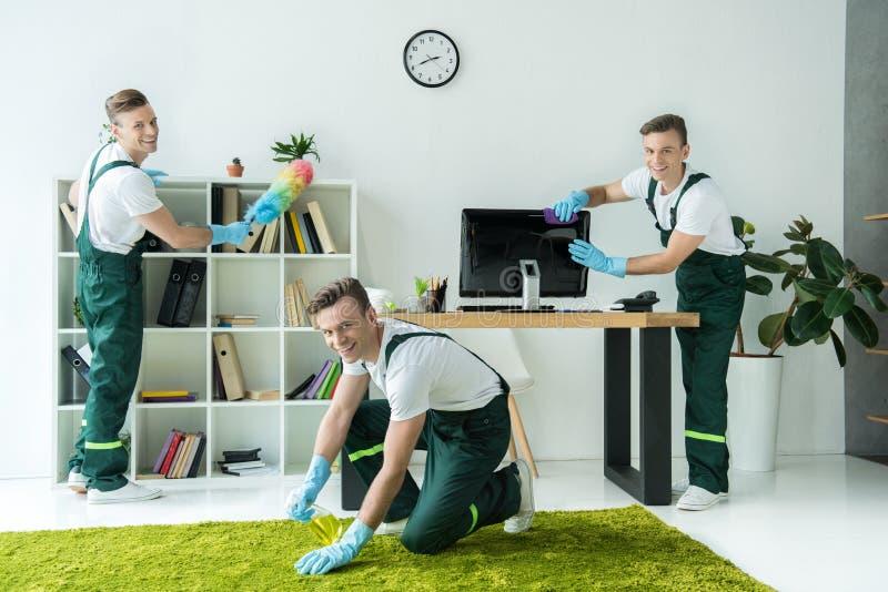 Collage van gelukkig jonge werknemer schoonmakend bureau en het glimlachen stock foto