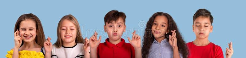 Collage von Studiogefühlporträts der multiethnischen Gruppe des Schulkindes, auf blauem Hintergrund stockbilder