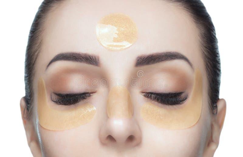 Collageen gouden flarden op de huid van het ooglid, het voorhoofd en de kin op het gezicht stock afbeeldingen