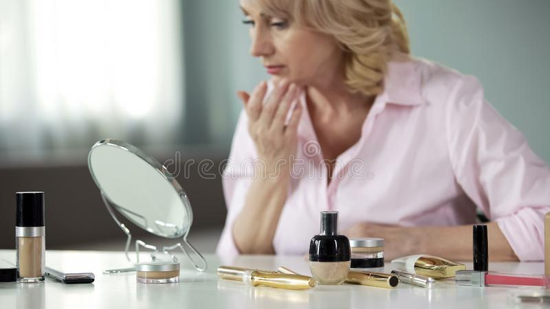Collagen cosmetics on table with woman examining her sagging skin background. Stock photo stock photo
