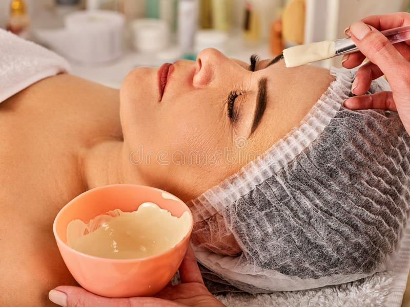 Collagen face mask. Facial skin treatment. Woman receiving cosmetic procedure. Collagen facial mask for skin treatment by natural mud. Elderly woman 50-60 years royalty free stock image