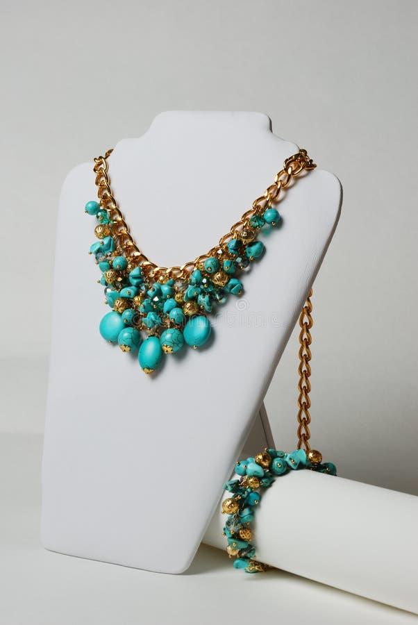 Collana con turchese, le pietre preziose naturali e la catena dell'oro su un manichino immagini stock libere da diritti