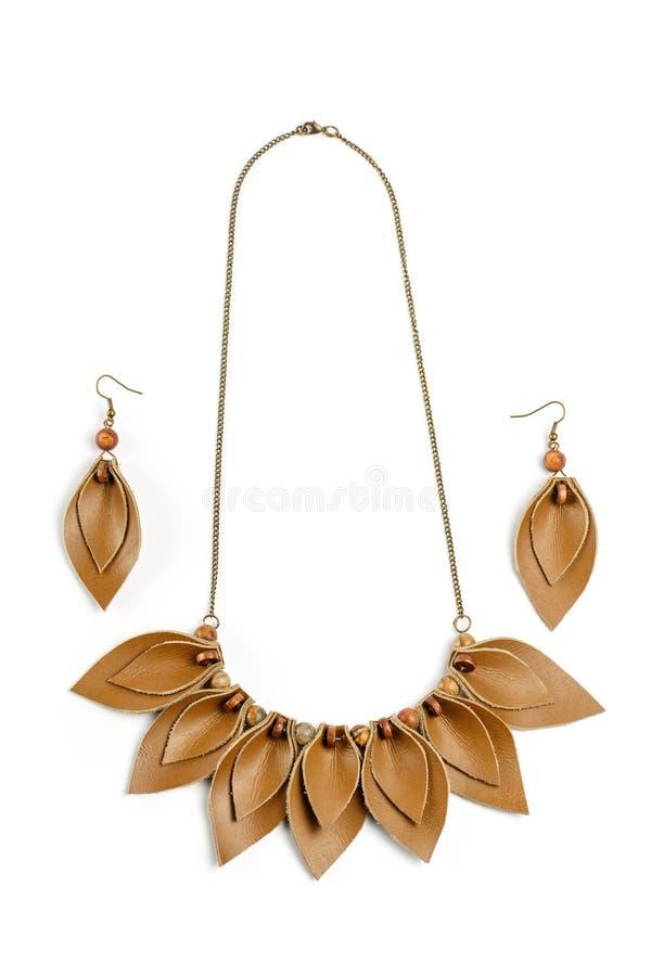 Collana dell'artigianato ed orecchini originali sotto forma di petali fatti di cuoio marrone su fondo bianco immagine stock