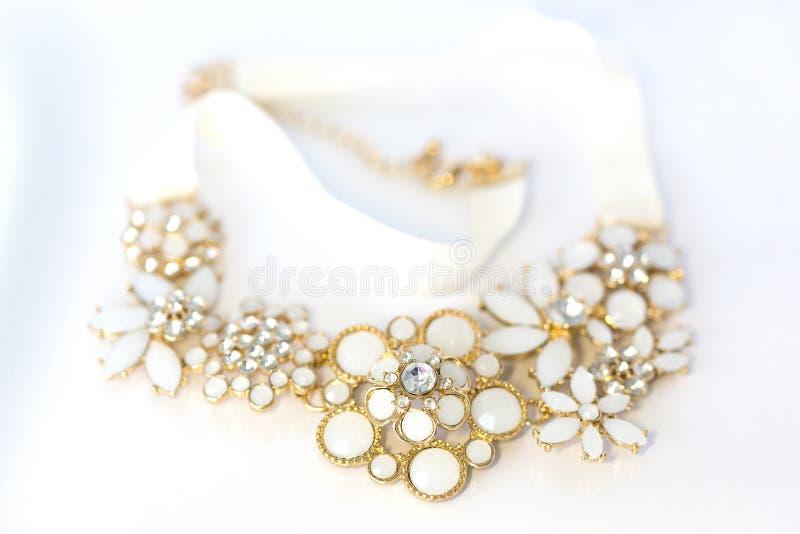 Collana dell'oro nella forma del mazzo dei fiori con gli elementi bianchi dello smalto ed i grandi cristalli di rocca fotografie stock libere da diritti