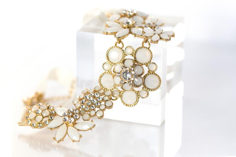 Collana dell'oro nella forma del mazzo dei fiori con gli elementi bianchi dello smalto ed i grandi cristalli di rocca fotografia stock