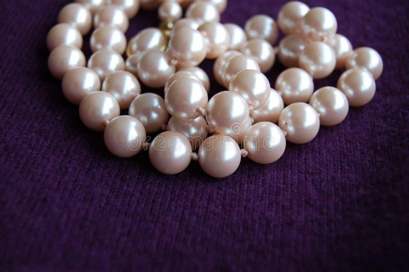 Collana della perla accatastata sul fondo porpora del cashmere immagine stock