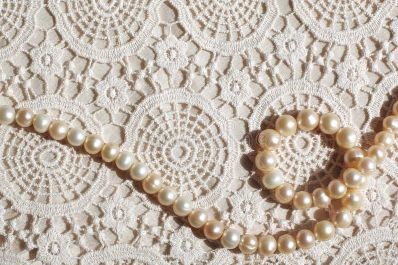 Collana della perla sul tessuto del pizzo fotografia stock libera da diritti