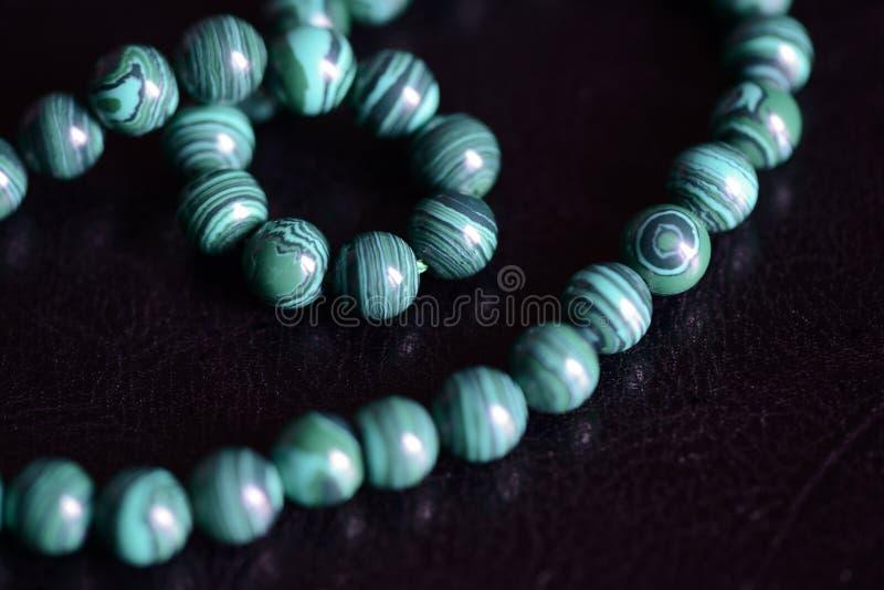 Collana di pietra delle perle della malachite su un fondo scuro immagini stock libere da diritti