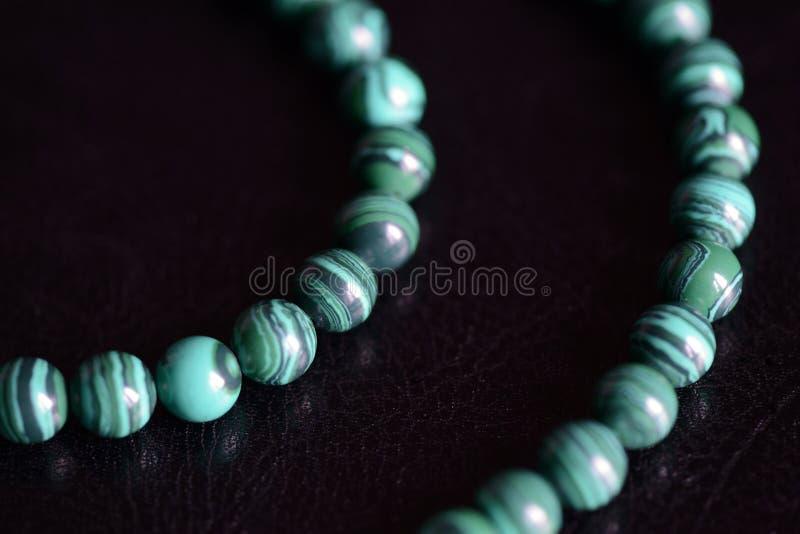 Collana di pietra delle perle della malachite su un fondo scuro fotografia stock libera da diritti